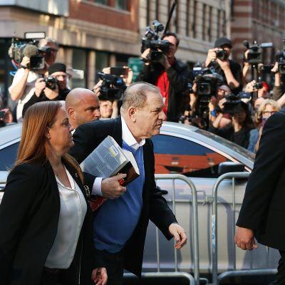 harvey Weinstein med en hög böcker under armen och pressen i bakgrunden överlämnar sig till polisen i New York.