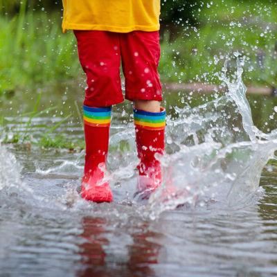 Barn hoppar i vattenpöl