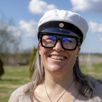 Maija Lahdensuo hymyilee kuvassa, taustalla peltomaisema