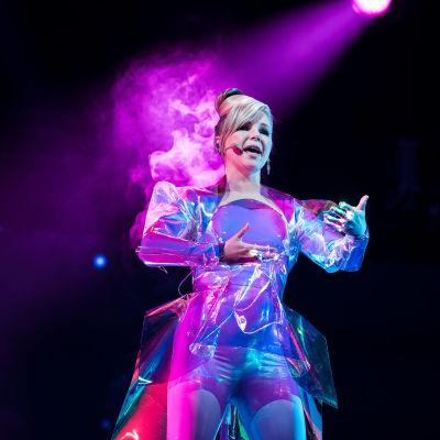 Pandora laulaa lavalla hopeisessa avaruushenkisessä asussa kädet edessään ilmassa elehtien.
