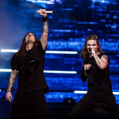 Blind Channelin laulajat lavalla mustiin pukeutuneina, toisella kasvot ja toinen käsi kohti kattoa, toinen laulaa mikkiin.
