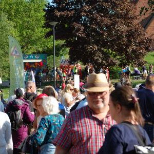 En folkmassa utomhus på granidagen i Grankulla. Det är sommar och mäniskor är iklädda solglasögon och hattar.