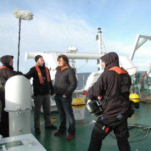 Elokuvan kuvausryhmä seisoo tuulitakeissa laivan kannella. Yksi jäsenistä pitelee käsissään mikkipuomia, toinen kameraa. Taustalla on meri.