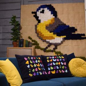 Kuddar med fågelmotiv i soffa i ett vardagsrum.