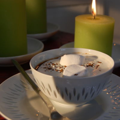 En kopp med varm choklad toppad med marshmallows, vispgrädde och lite kaffepulver.