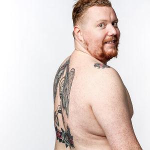 Visa Viljamaa esittelee tatuointejaan studiokuvassa.