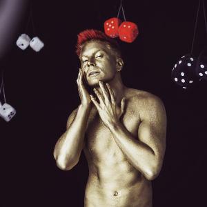 Antti Tuisku kullatussa kropassa ja punaisilla hiuksilla poseeraa mustalla taustalla Kesäkumibiisin videolla. Antin ympärillä on karvanoppia.