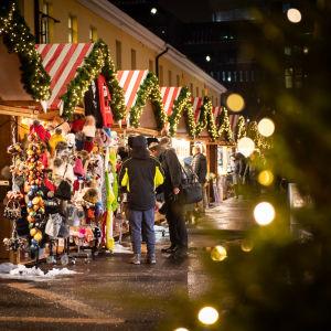 Internationella julmarknaden i Helsingfors. Juliga små försäljningsstånd och kunder som tittar på varor med ryggen mot kameran.