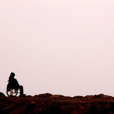 Ensam person i rullstol vid havet.