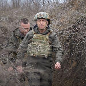 Zelenskyi kulkee maastopuvussa, luotiliveissä ja kypärässä ryteikköisessä juoksuhaudassa. Taustalla näkyy kaksi miestä. Miehellä Zelenskyin takana ei ole kypärää päässään.