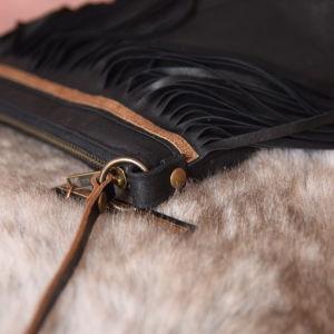 Detaljer av en svart läderhandväska med fransar.