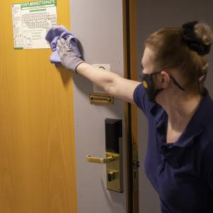 Sol-siivouspalveluiden kohdevastaava Riia Korhonen puhdistaa hotellinoven opaskylttiä.