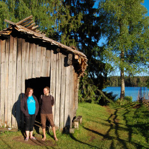 Puinen mallassavusauna järven rannalla, omistajat Merja ja Juha Väinämön seisovat saunan edessä.