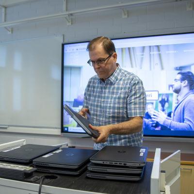 Rehtori Pekka Manninen nostaa kannettavia tietokoneita pöydälle