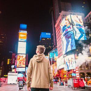 En ung man stirrar på reklamerna på Times Square