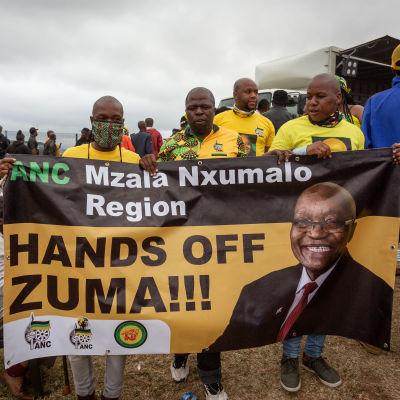 Kannattajat pitelevät lakanaa, jossa on Zuman kuva.
