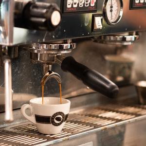 Kaffemaskin. Kaffet rinner ner i en kopp.