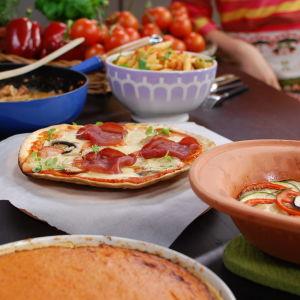En köksbänk med flera tomaträtter uppdukade, så som tomatpaj, ratatouille, pizza, korv stroganoff och tomatpasta.