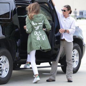 """Melania Trump på väg ini en bil. Budskapet """"Jag bryr mig inte"""" delvis synligt på ryggen."""