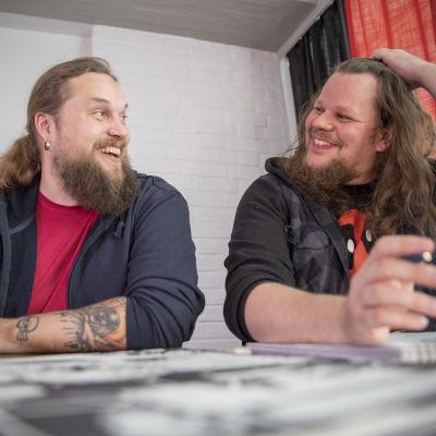 Roope-Santeri Nieminen ja Esa Turunen pöydän ääressä piirtämässä sarjakuvia iloisina.