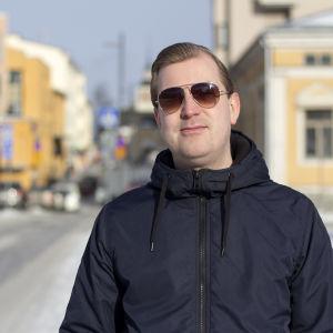 En man som bär solglasögon. I bakgrunden syns flera gula hus. Det är en solig vinterdag.
