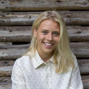 En ung kvinna med blont hår och vit skjorta sitter framför en lada gjord av stockar. Det är sommar.