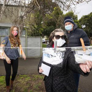 Nainen irrottaa maskia sisältävää muovipussia pyykkinarulta, taustalla kolme muuta ihmistä maskit kasvoillaan
