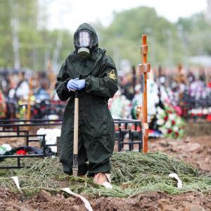 Bild på person i full skyddsdräkt. Personen står vid en grav där en person som dött till följd av covid-19 begravs.