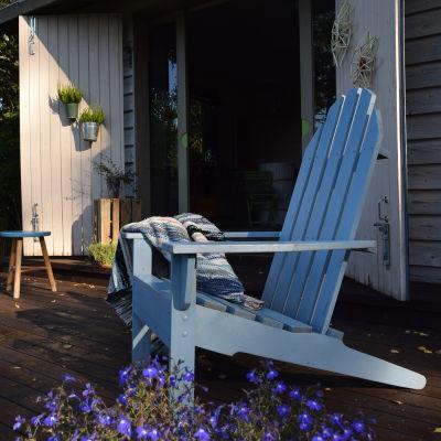 En ljusblå solstol i trä som står på en bastuveranda.