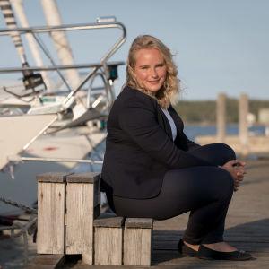 Michelle Grönlund sitter på en brygga. Båtar i bakgrunden.