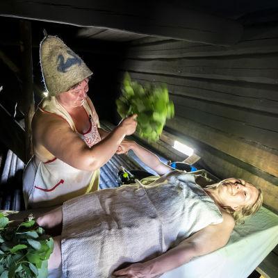 Saunottaja vihtoo makaavaa naista savusaunassa.