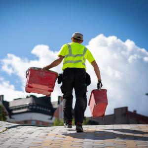 Rakennustyömies kantaa kahta ämpäriä