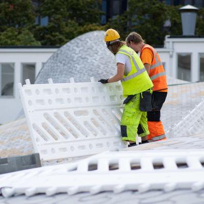 Rakennustyömiehet laittavat suoja-aitoja