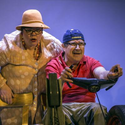Två skådespelare på scen. Den ena av dem håller i en ratt.