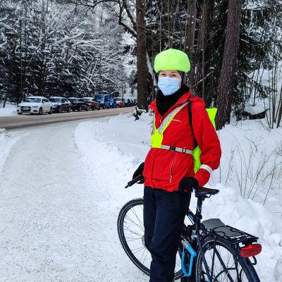En cyklist iförd röd jacka står vid sin cykel i ett vinterlandskap