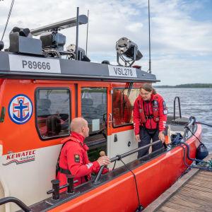 Två sjöräddare fixar med något på en sjöräddningsbåt.