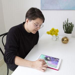 Zarah Holmberg sitter vid ett bord och ritar med sin ipad.