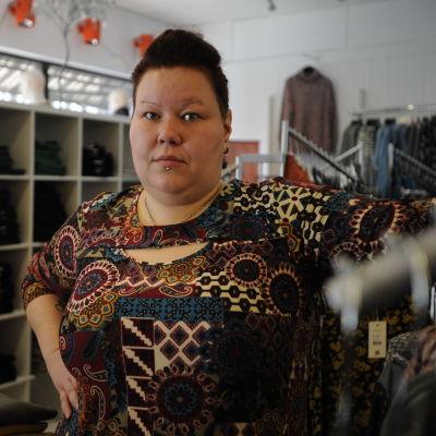 Erica Wickman står bredvid e n klädställning i sin butik