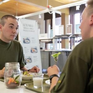 Kuvassa korpraali Kinnunen ja alikersantti Makkonen syömässä muonituskeskuksessa.