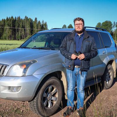 Tomas Nyström står vid sin bil intill en åker
