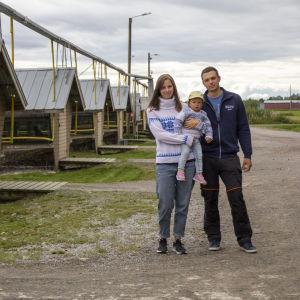 En man och en kvinna som håller ett barn i famnen står framför en rad av hus där rävar förvaras.