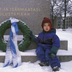 Ett litet barn vid hjältegraven på självständighetsdagen 1997.