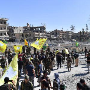 Medlemmar av syriska demokratiska styrkorna SDF uppbackade av amerikanska styrkor  samlas vid ett torg i Raqqa 17.10.2017.