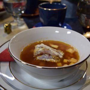 En portion sotad sik med vitlöksmajonnäs och friterade fiskfjäll i mörk fiskbuljong.