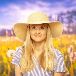 Karin Storbacka står på en sommaräng med en stor solhatt på huvudet.