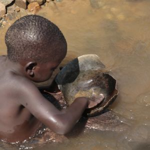 Pieni lapsi huuhtoo kultaa joessa Zimbabwessa.