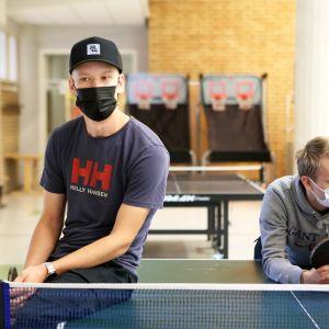 Otto Salminen ja Kalle Mäkelä nojaavat pingispöytään.