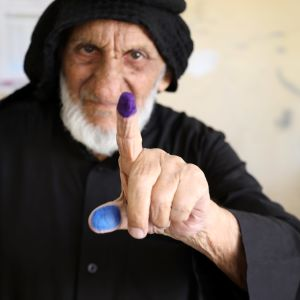 En äldre irakisk man visar upp ett färgat pekfinger och en tumme som bevis på att han har röstat.
