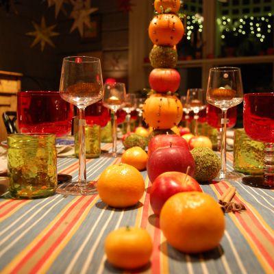 Bordsdekorationer med äpplen, apelsiner och ljusfrukter