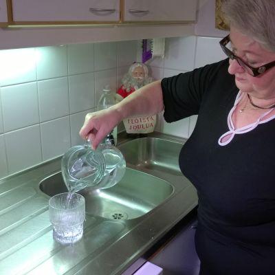 nainen kaataa vettä kannusta lasiin